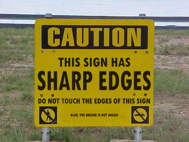 Warning sign - WARNING this sign has sharp edges. Do not touch the edges of this sign. Also, the bridge ahead is out.